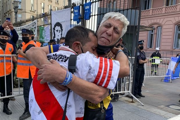 Soccer fans of rival soccer teams Boca Juniors, right, and River Plate, left, embrace as they wait to enter the presidential palace to see Diego Maradona lying in state in Buenos Aires, Argentina, Thursday, Nov. 26, 2020. The Argentine soccer great who led his country to the 1986 World Cup title died Wednesday at the age of 60. (AP Photo/Debora Rey)