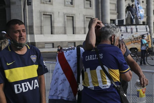Soccer fans embrace as they wait to see Diego Maradona lying in state outside the presidential palace in Buenos Aires, Argentina, Thursday, Nov. 26, 2020. The Argentine soccer great who led his country to the 1986 World Cup title died Wednesday at the age of 60. (AP Photo/Rodrigo Abd)